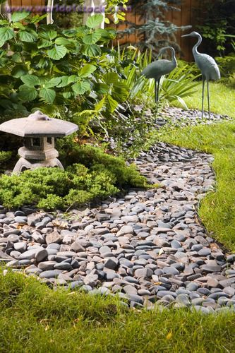 stock photo titled a backyard japanese garden with a dry stream bed lantern and