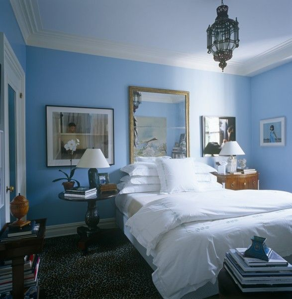a blue guest room with white linens and accents and leopard carpet in NYC designer Brian
