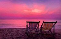 purple sunset over water with beach chairs