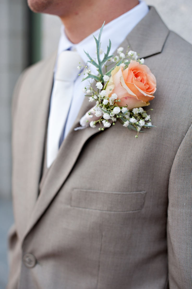 Light grey suit for Cyle cream or white ties coral flower and no jackets for the groomsmen
