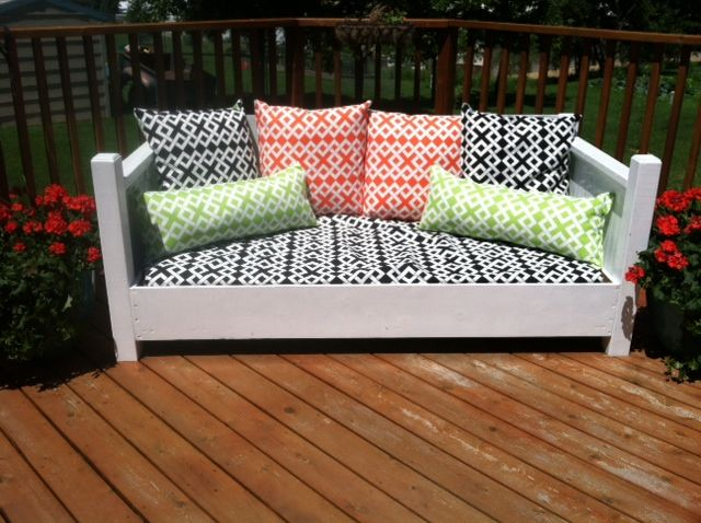 A repurposed twin bed made into an outdoor sofa With waterproof mattress and outdoor fabrics