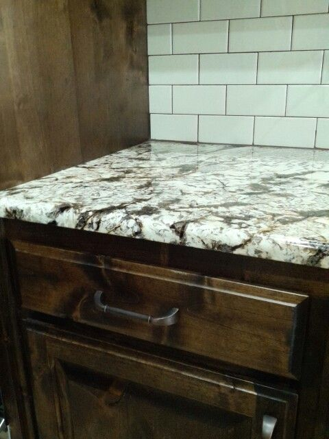 Delicatus normandy granite biscuit subway tile backsplash walnut stained knotty alder cabinets