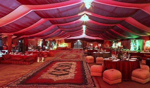 Arabian Nights  Arabian attire bazaar tent with market items baskets lamps urns rugs