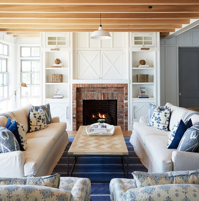 Cottage living room features a pair of white slipcovered sofas adorned with blue pillows facing