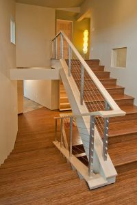 Tension wire stair railing with a funky modern floor lamp