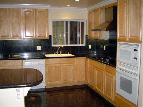 Kitchen With Black Granite And Natural Oak Cabinets