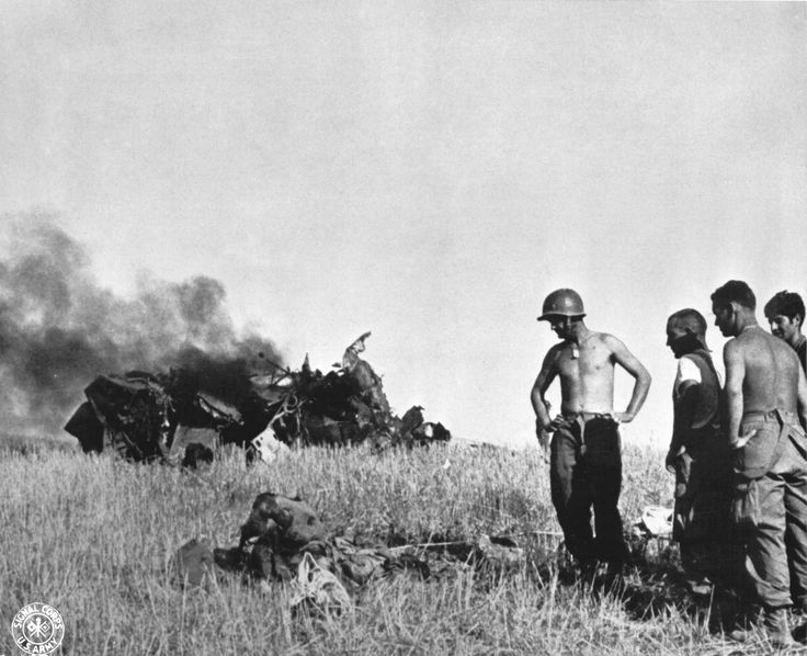 US soldiers looking at a dead German pilot and his wrecked aircraft near Gela Sicily on 12 July