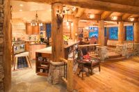 Warm log home kitchen with natural stone and large log ...