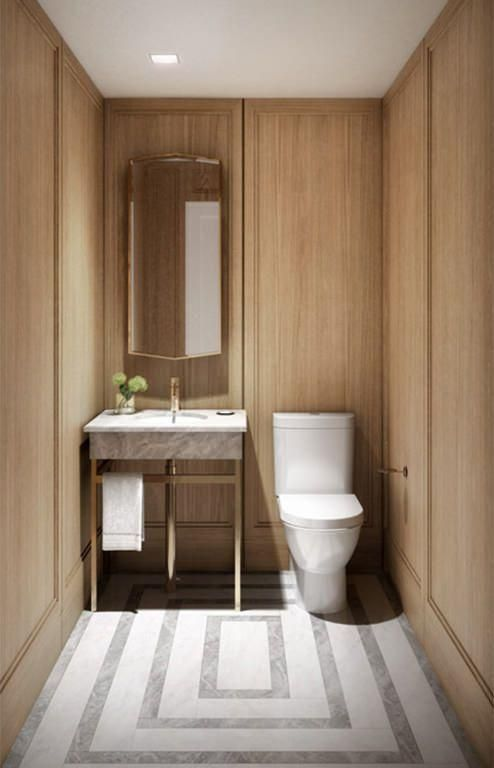 Warm wood walls with millwork brass sink fixture and