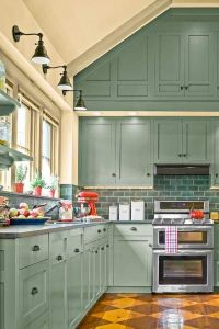 A dramatic accent wall of cabinets in sage blue/green with ...