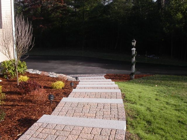 Granite steps paver walkway granite wall and garden all combine to create a grand entrance to