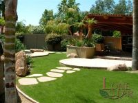 This backyard is an oasis with grass, flagstone stepstones ...
