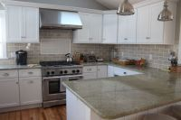 This kitchen features Coast Green granite countertops and ...