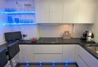 White gloss handless kitchen in acrylic finish, with ...