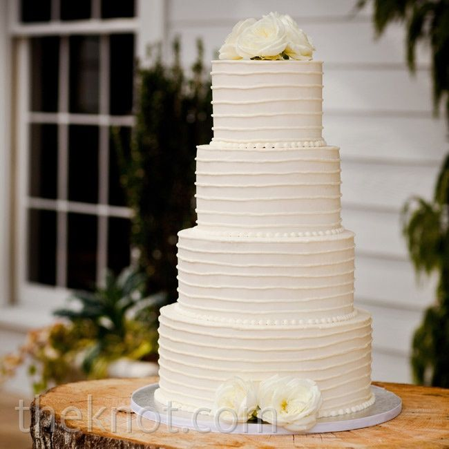 The allwhite cake got just a few simple touches combed buttercream frosting and a handful of