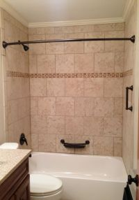 Tile tub surround. Beige tile bathtub surround with oil ...