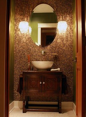 Half bath with great vanity that has a bowl sink and a beautiful shiny copper and brown glass
