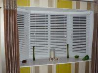White Venetian Blinds Covering Bay Windows Revealed Behind