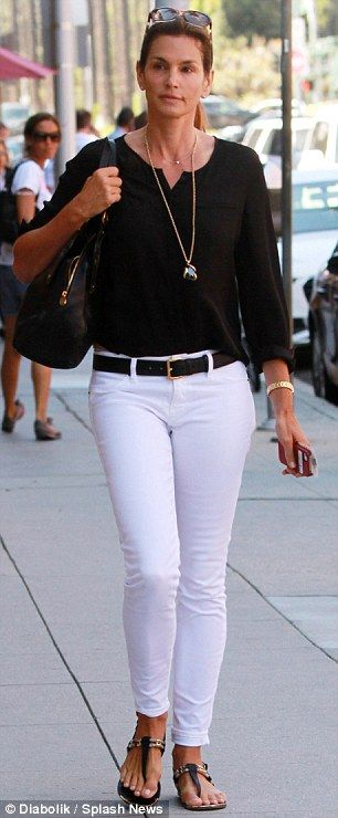 LESS IS MORE! Seasonless style: The mother-of-two looked chic in a black blouse and white skinny jeans, …