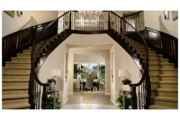 A twin staircase frames a hallway leading to a two-story ...