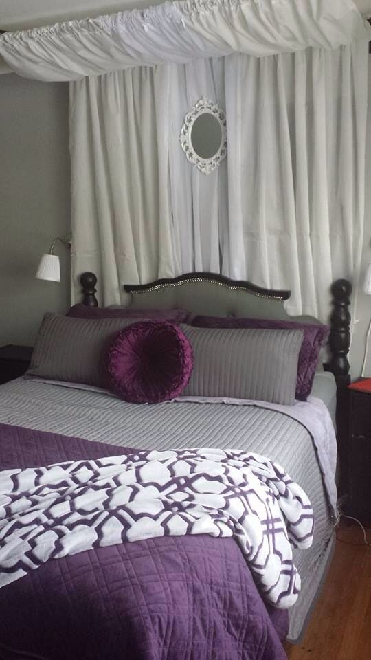 Grey, purple, black, and white master bedroom. Wall lamps