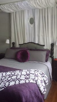 Grey, purple, black, and white master bedroom. Wall lamps ...