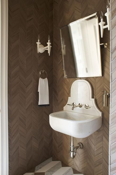White and brown powder room boasts walls clad in brown herringbone tiles lined with a