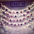 Polaroid pictures hanging from fairy lights by pegs fairy lights