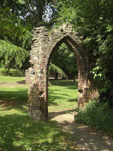 A Stone Garden Arch Resembling Part Of An Old Ruin Makes