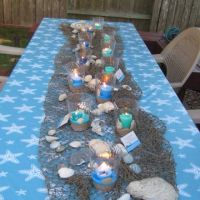 cut out starfish on blue tablecloths. Seagrass mats or ...