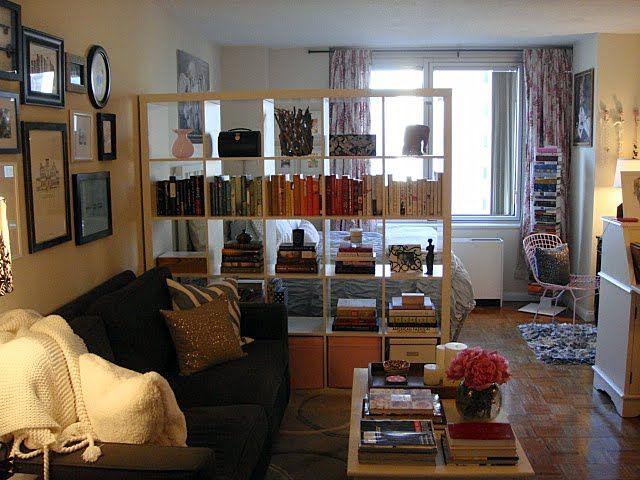 Studio apartment  oversized bookshelf as room divide which still lets window light in  La casa