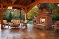 Wood and stone backyard covered patio and fireplace ...