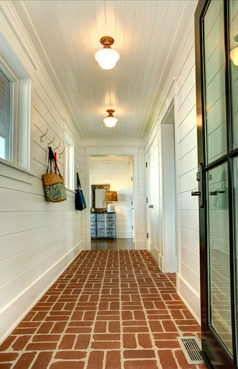 Stunning mudroom features a black glass door opening to reveal red brick floors alongside tongue