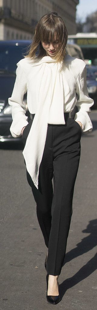 Paris Fashion Week street style:  Anya Ziourova wearing classic black pants and a white tie collar shirt paired with classic black
