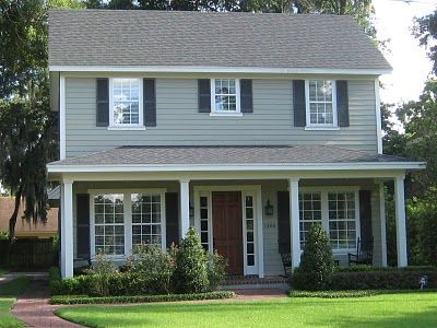 Green House With Cream Trim Black Accents And Brown Roof