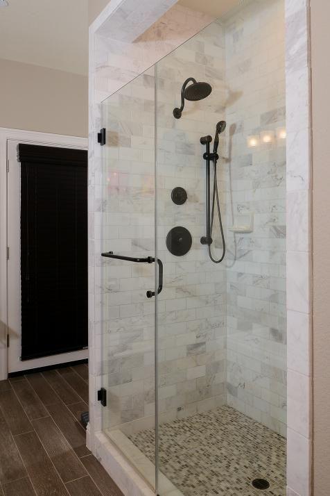This glassenclosed shower features beautiful Carrara