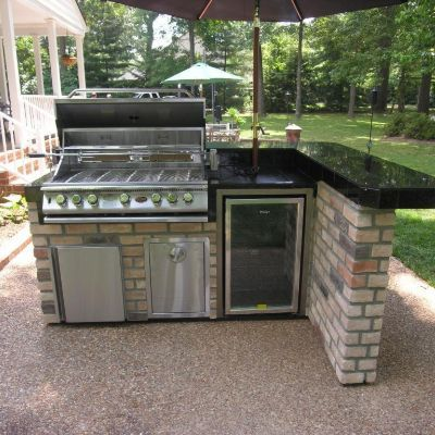 This Lshaped outdoor kitchen features a bar counter sitting area Besides the grill the unit