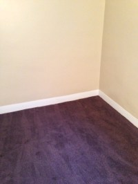 light tan walls with white trim and dark burgundy carpet ...