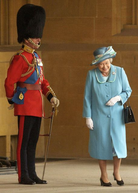 The Queen gets a look at her husband, in uniform.  It's a good marriage if you can still crack each other up.