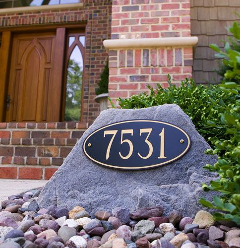 faux rock with address in landscaping