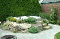 above ground jacuzzi swim spa with rocks and waterfall