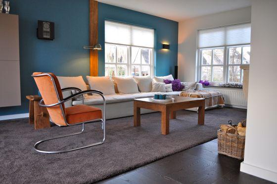 woonkamer met blauwe muur gispen stoel en witte bank