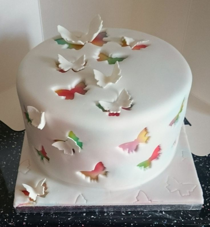 airbrushed cake covered in white fondant with butterflies cut out…