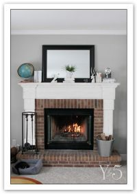 Grey walls, white mantle, natural brick fireplace. The ...