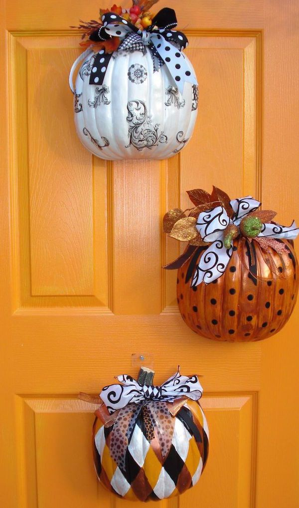 Buy fake pumpkins from the $1 store, cut them in half, decorate the outside, and hang them on your front door! SO smart and pretty!: