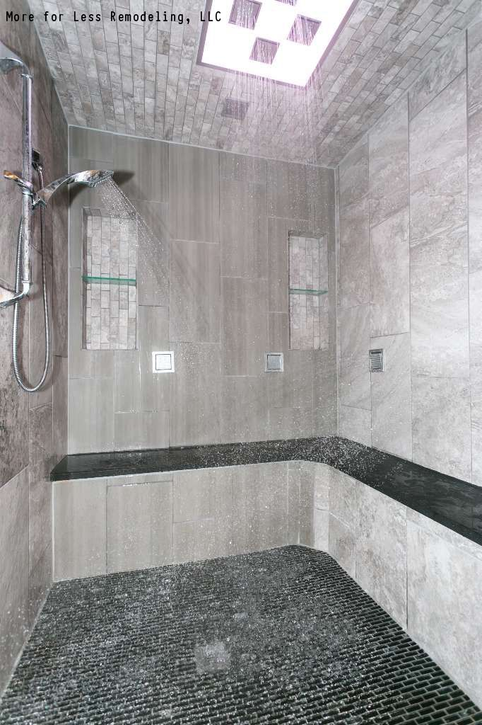 A modern walk in shower with a large shower bench and