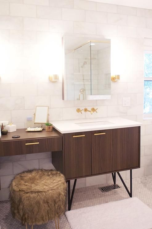 Vanity adorned with brass pulls topped with white quartz