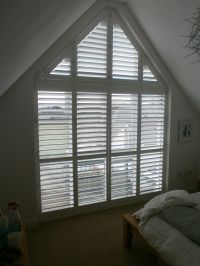 A tall gable end window with phoenix wood shutters