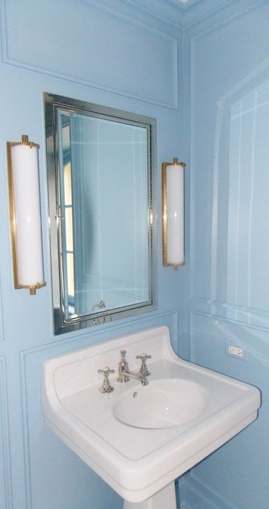 Gorgeous bathroom features blue paint on walls accented with decorative moldings framing a
