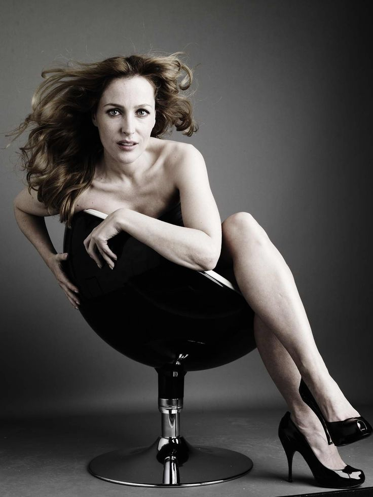 Gillian Anderson nude with pumps sitting in a chair